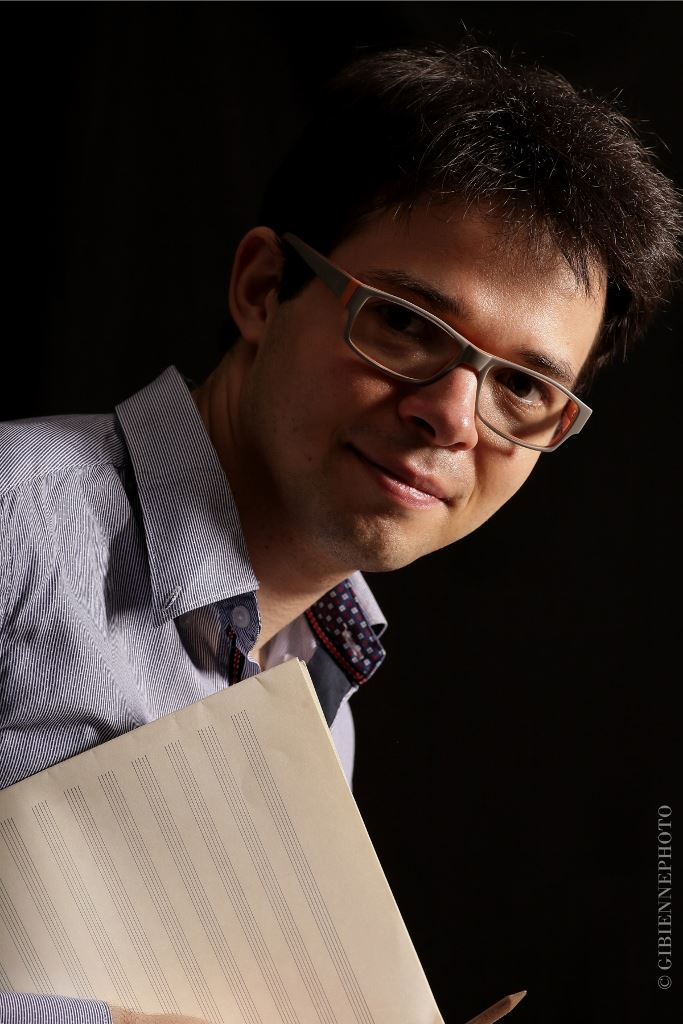 Peter Bajetta portrait photo holding music manuscript paper.